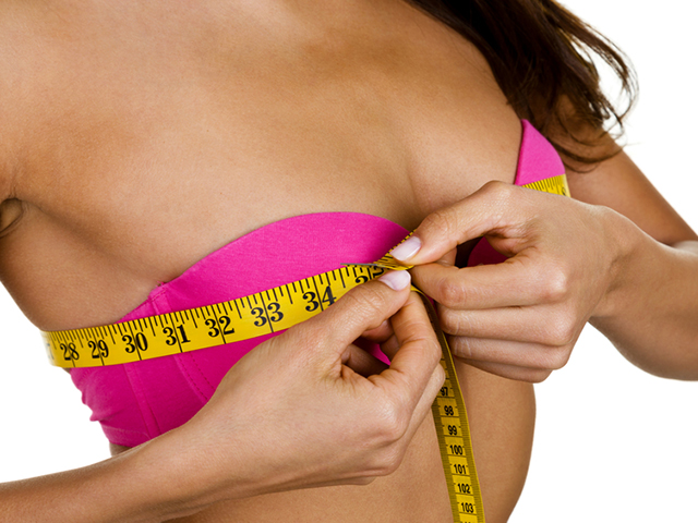 Woman measuring her breast size