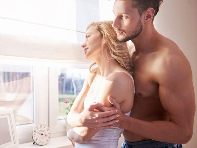 朝窓辺で抱き合うカップル