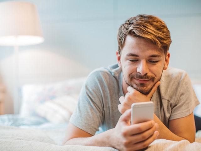 ベッドで携帯チェックする男性