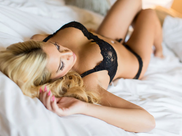 Beautiful blond woman wearing black lace lingerie on bed