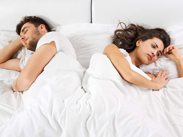 Upset couple lying  in bed