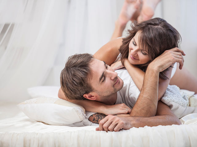 Couple man and woman lay cuddling on the bed