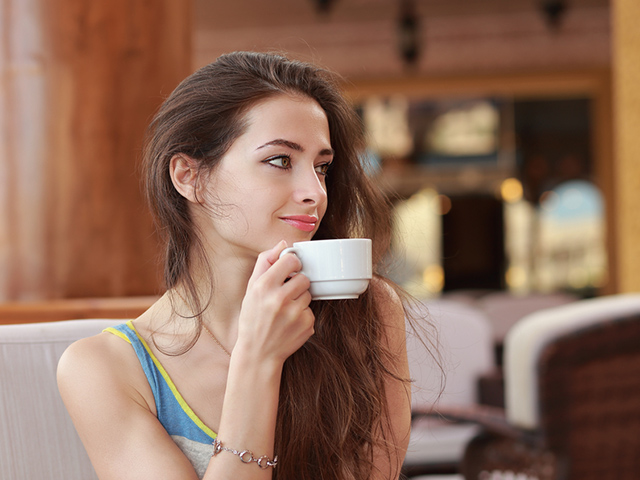 Woman with cup of coffee sitting in cafe and looking
