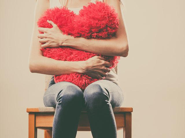 クッションを抱きしめる女性