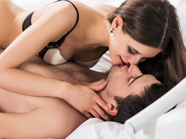 Young romantic couple hugging and kissing on a white bed, having sex and being loving with each other.