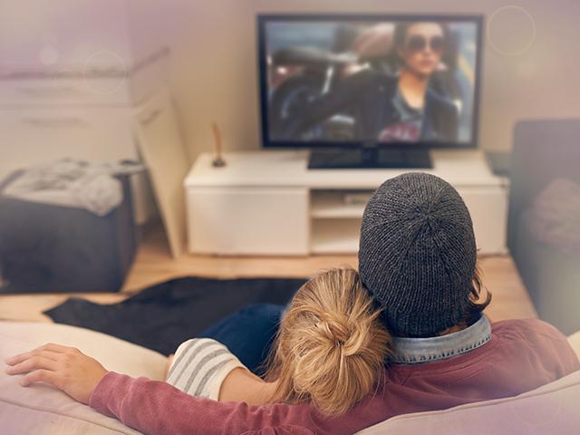 部屋で映画鑑賞するカップル